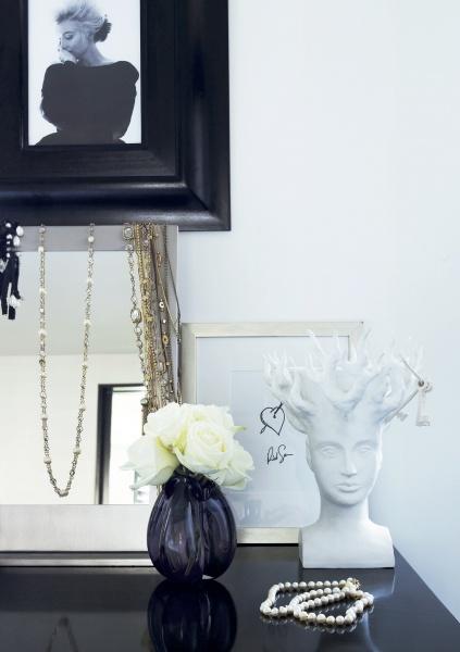 På motsatta sida i rummet står ett spegelblankt toalettbord med fotografier och dekorativa glasvaser, smycken och tavlor. En förvaringsmöbel som även blir ett levande stilleben med personliga inslag.