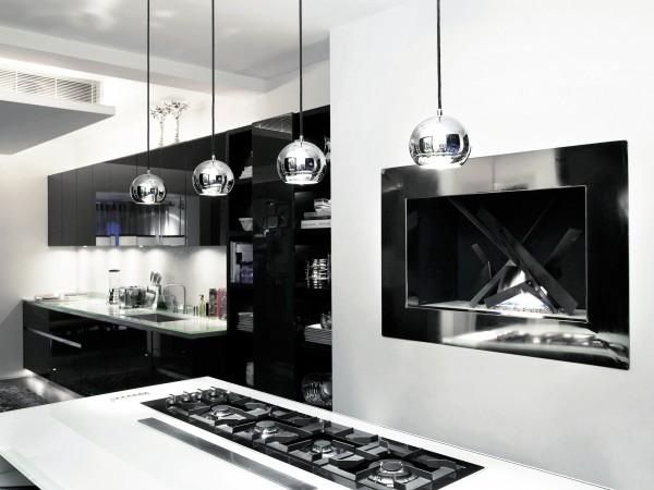 Det eleganta köket med högblanka luckor är platsbyggt från Boffi. Köksmiljön är praktiskt planerad med en stor köksö som rymmer förvaring och spis. Lampor från Rob Clift. På andra sidan köksön står två barstolar från Talisman.